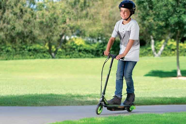 kid enjoys riding on a razor a5 lux scooter in a park