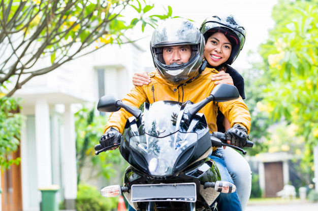 couple wearing helmets riding a scooter