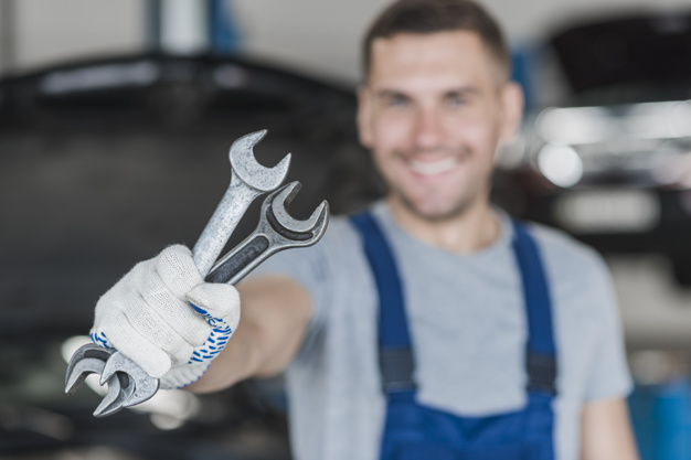 mechanic holding two wrench